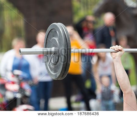 The man's hand lifts the bar in the park