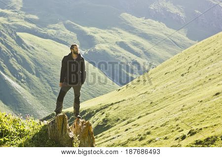 man with beard in black jacket standing with hands up above mountain slopes at yellow sunset