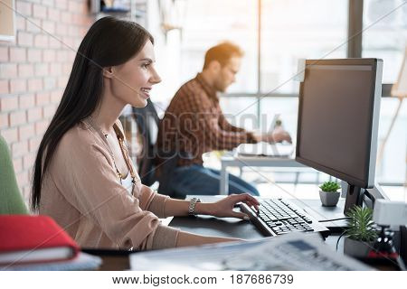 Hilarious female worker is working on computer. She sitting at office. Profile