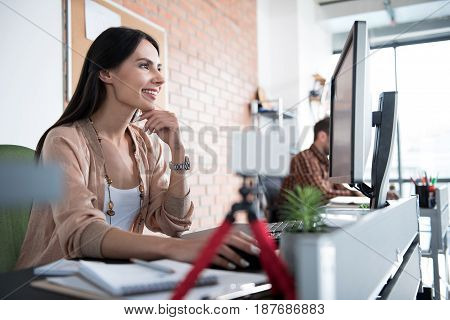 Cheerful woman is sitting near table and glancing at screen of computer. He looking with smile