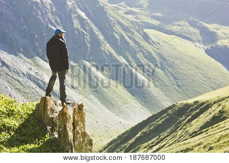 man in black jacket standing with hands up above mountain slopes at yellow sunset