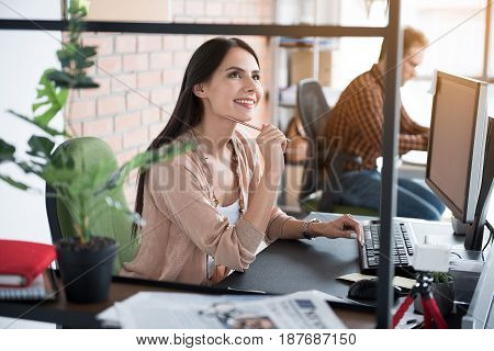 Jolly woman is sitting near desk in office among colleagues. She holding pencil and looking up with bright smile. Portrait