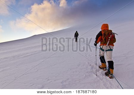 man in red jacket with ice-axe and backpack climbing on snow slope of Kazbek mountain in Caucasus at sunrise