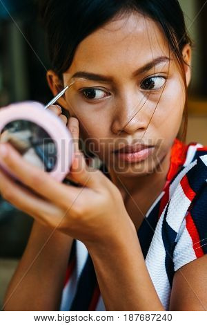 Young beautiful girl applying makeup. Girl coloring eyebrows with eyebrow liner