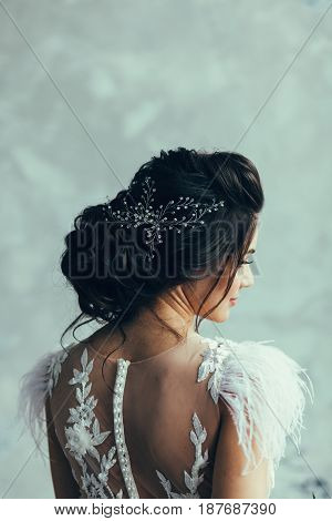 Portrait of the bride in a wedding dress and with a hairdress from the back