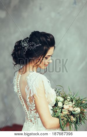 Portrait of the bride in a wedding dress and flowers in loft interior