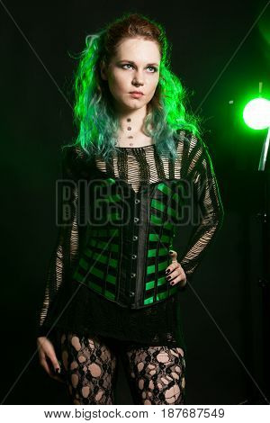 Beautiful Woman in cosplay corset posing in studio with a green light from behind. Studio photo. Fashion and cosplay