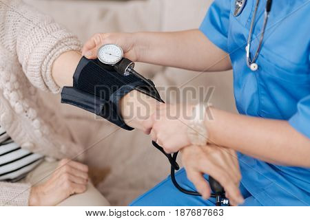 Blood pressure. Qualified prominent nice doctor running some tests while conducting a checkup on elderly womans health whom she visiting every week
