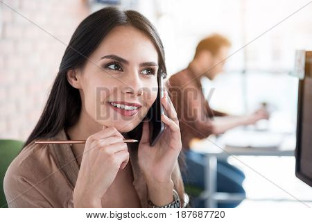 Cheerful female office worker is talking on telephone and looking aside with smile. She holding pencil. Portrait