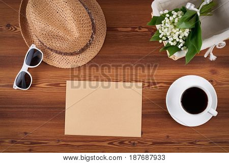 Top view craft envelope with blank copy space for text, straw hat, sunglasses and white spring flowers on wooden background