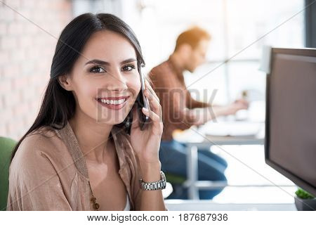 Cheerful female worker is sitting near desk. She talking on phone and looking at camera with bright smile. Portrait
