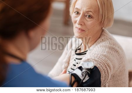 Precise figures. Cute elegant mature woman sitting on her bad and undergoing some needed tests while the doctor measuring her blood pressure