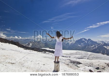 girl in white dress standing on snow slope of caucasus mountains with hands-up with mountains surrounding and blue sky