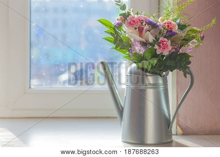 still life flowers in watering can on the windowsill