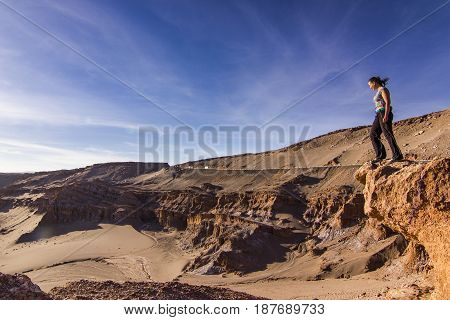 girl standing on a cliff with panoramic view in Moon valley in atacama desert in Chile at sunset looking on sun
