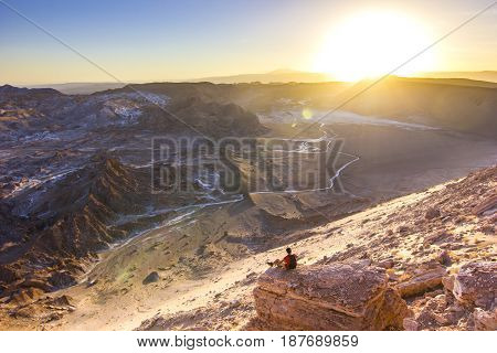 man sitting on a cliff with panoramic view in Moon valley in atacama desert in Chile at sunset looking on sun