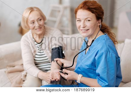 Medical proficiency. Enchanting energetic prominent woman employing blood pressure monitor for checking her patients health condition while visiting her at home