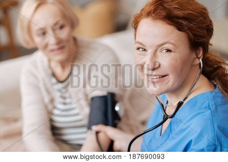 Years of training. Charismatic qualified careful woman using stethoscope and tonometer for indicating patients blood pressure measurements while running a general examination