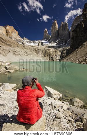 girl in red jacket sitting near blue lake in patagonia making photo with camera