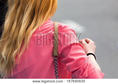 The strap from the bag hangs on the girl's shoulder .