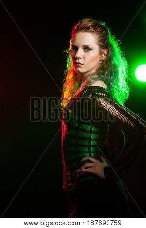 Cosplay model in corset in studio photo with a red and green light from behind. Cosplay and subculture