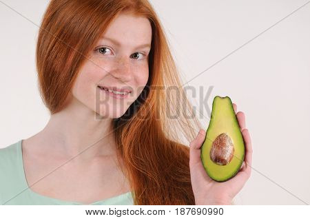 Beautiful smiling young girl posing with a half of avocado. Red hair teenager girl hold avocado. Close up portrait
