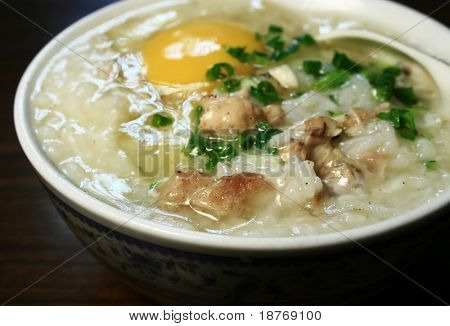 bowl of hot pork con-gee with fresh raw egg on top poster