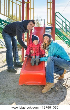 Joyful parents mother and father with excited little daughter having fun at sliding board outdoors at the playground