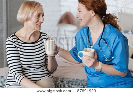 Curing with positive emotions. Kind thankful mature woman inviting the doctor for having a cup of tea after she helping her with treatment