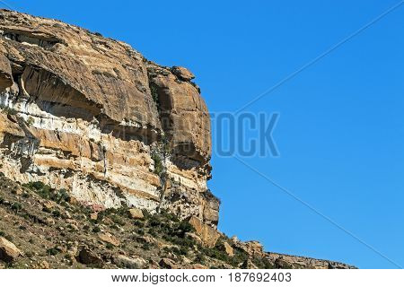 Dry winter orange colored rocky mountain and blue sky landscape in the Orange Free State in South Africa