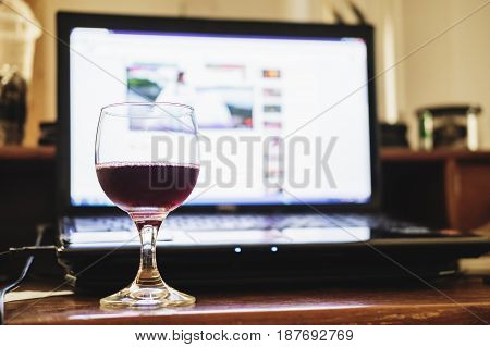 Red wine in glass with computer laptop on wooden table, relaxing in working space