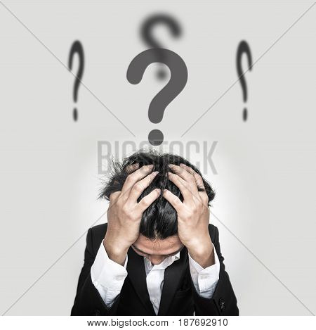 Confused businessman with question marks sign on head