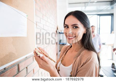 Jolly office worker is holding stickers and looking at camera with bright smile. She standing near special board. Portrait