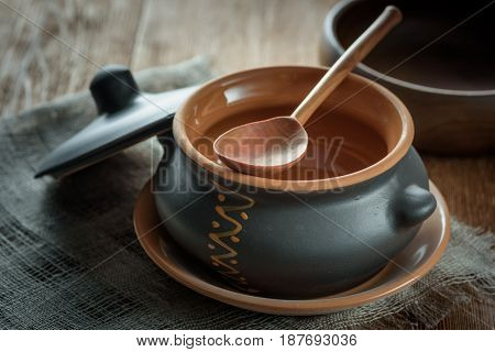 Clay pot for baking with lid with a wooden spoon on linen napkin on dark background
