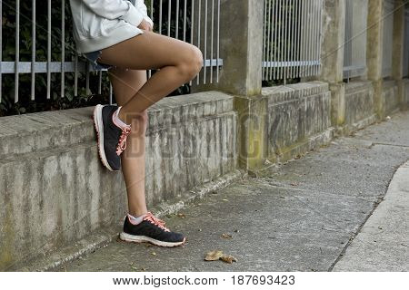 young woman leaning against a metal fence with on foot on the concrete pillar