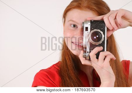 Portrait of young red haired girl holding vintage camera against grey background with focus on eye. Happy smiling lifestyle people concept.