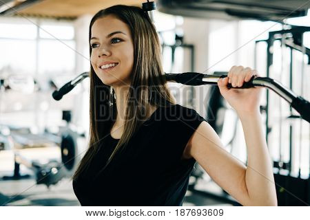 Young beautiful girl exercising in the fitness gym with lat machine