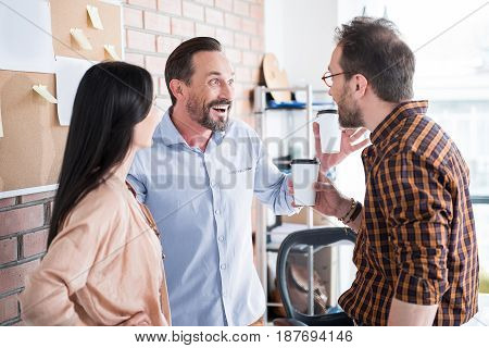 Working atmosphere. Cheerful man is telling certain joke with bright smile, he holding cup with coffee. Colleague looking at him attention