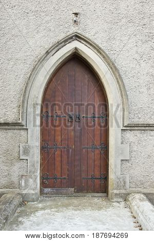 old unused wooden door and concrete arch of church with a pathway