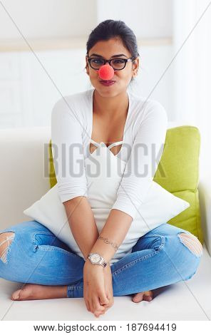 Beautiful Indiana Girl With Red Clown Nose Sitting On Couch At Home