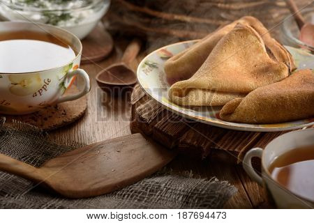Breakfast tea and hot ruddy delicious pancakes on the wooden table