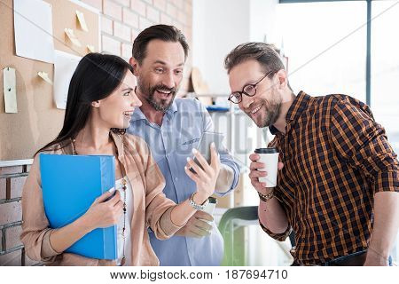 Cheerful woman is holding blue folder and standing among coworkers. Men are looking at screen of phone, she keeping with smile