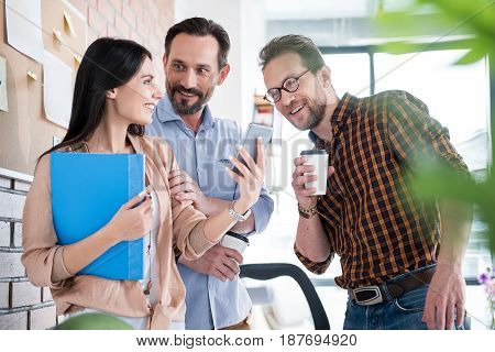Merry men are looking at screen of their female coworker phone with admiringly smile. She standing near them and holding blue folder