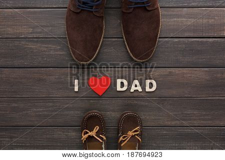 Happy Fathers Day, love dad background on rustic wood with male and child shoes