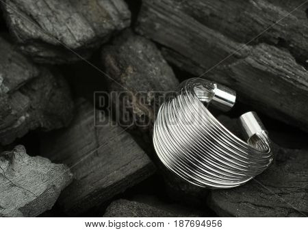 Silver jewelry ring on black coal background