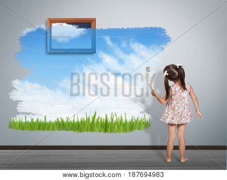 child girl with paint brush painting wall back view