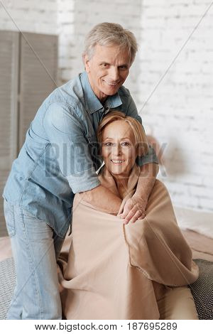 Protecting my treasure. Pleasant charismatic senior gentleman making sure his lady feeling comfortable while they spending time together at home