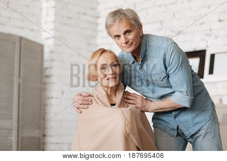 Watching out for my love. Wise charming senior man making sure his lady feeling warm while she asking him for a favor while spending time at home