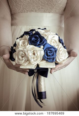 The bride's bouquet in hands on background of the wedding dress