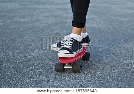 Two feet of a young woman standing on a red skate board while on a asphalt road